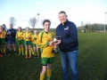 Captain Chloe OKeeffe receives U12 trophy from M Murphy .