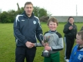 Captain Michael Sheahan receives cup from Dave Naughton Chairman of the LDSL
