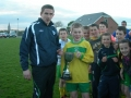 Killian Begley accepts cup from Tom Ambrose of the LDSL