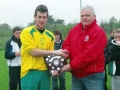 Captain Marcus Moore accepts the Under 17 Cup from LDFL committee member Chris Purcell.